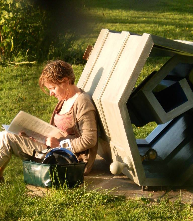Contemporary garden sculpture with woman reading.